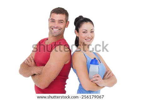Fit man and woman smiling at camera together on white background - stock photo