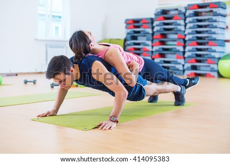 Fit man doing push-ups with woman on back in gym using own weight. Sport training arms, teamwork - stock photo