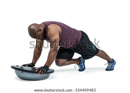 Fit man exercising with bosu ball on white background - stock photo