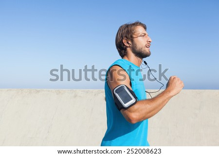 Fit man jogging on promenade on a sunny day - stock photo