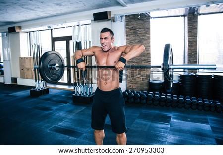 Fit man lifting barbell at gym - stock photo