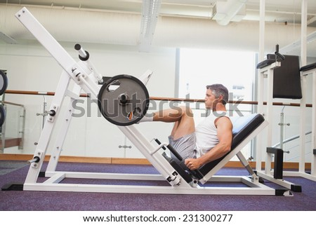 Fit man lifting heavy barbell with legs at the gym - stock photo