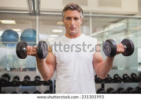 Fit man lifting heavy black dumbbells at the gym - stock photo