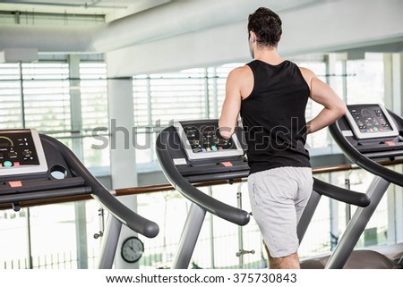 Fit man running on treadmill at the gym - stock photo