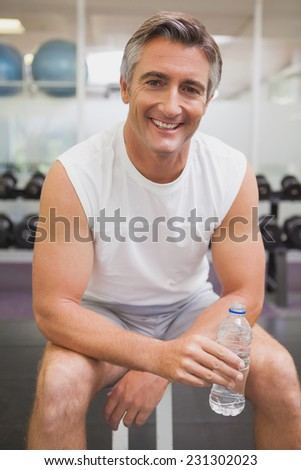 Fit man taking a break in the weights room at the gym - stock photo