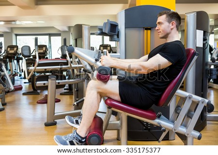 Fit man using weights machine for legs at the gym - stock photo