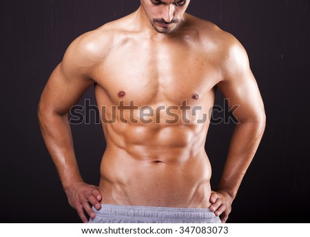 Fit man with beautiful torso on grunge background - stock photo