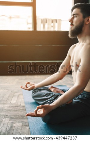 Fit man with dark hair and beard wearing trousers doing yoga position and sitting on blue matt at window background, position of fingers in mudra, copy space, portrait. - stock photo