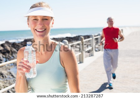 Fit mature couple jogging together on the pier on a sunny day - stock photo