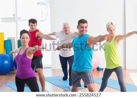 Fit men and women doing warrior pose in yoga class - stock photo