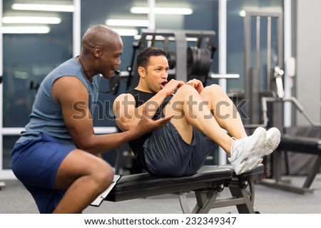 fit middle aged man with personal trainer in gym - stock photo