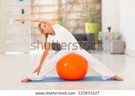 fit middle aged woman workout on exercise ball - stock photo