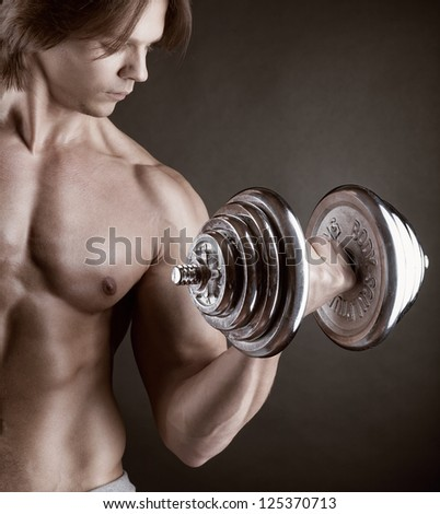 Fit muscular man exercising with dumbbell on dark background - stock photo