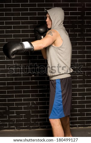 Fit muscular young boxer wearing a short sleeved hoodie working out against a brick wall throwing a punch with his gloved hand - stock photo