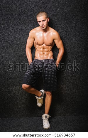 Fit muscular young shirtless man posing. Young Caucasian bodybuilder guy with short hair standing against black background wearing gray shorts. Medium retouch, no filter. - stock photo