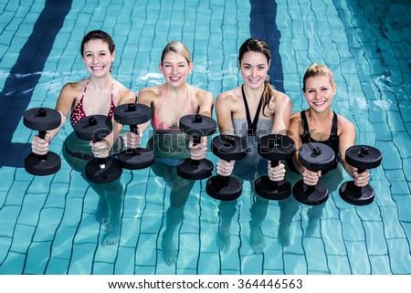 Fit people doing an aqua aerobics class in swimming pool - stock photo