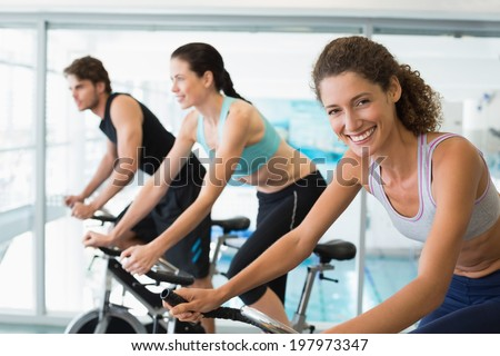 Fit people in a spin class with woman smiling at camera at the gym - stock photo