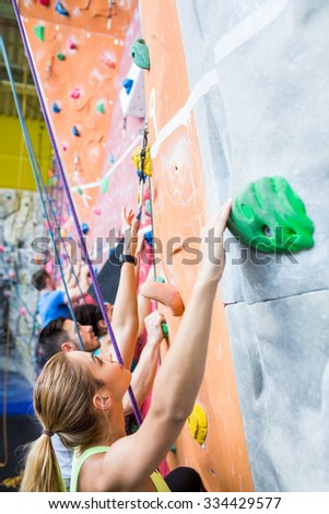 Fit people rock climbing indoors at the gym - stock photo