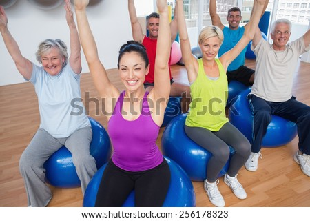 Fit people sitting on exercise balls with hands raised in fitness class - stock photo