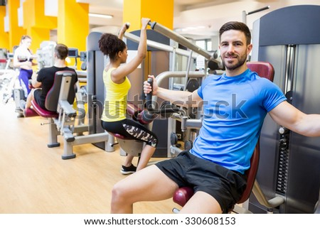 Fit people using weights machines at the gym - stock photo