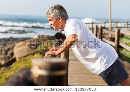 fit senior man exercising at the beach in the morning - stock photo