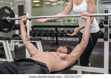 Fit shirtless man lifting barbell with his trainer spotting at the gym - stock photo