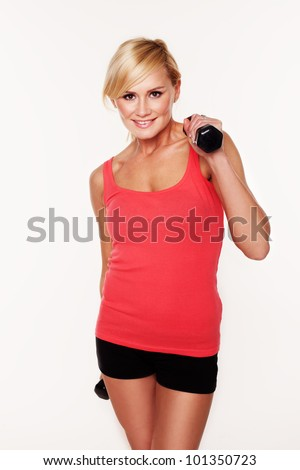 Fit smiling blonde woman in shorts lifting a pair of dumbbells to shoulder height as she exercises and works out, isolated on white - stock photo