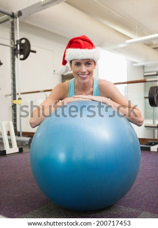 Fit smiling brunette in santa hat leaning on exercise ball at the gym - stock photo