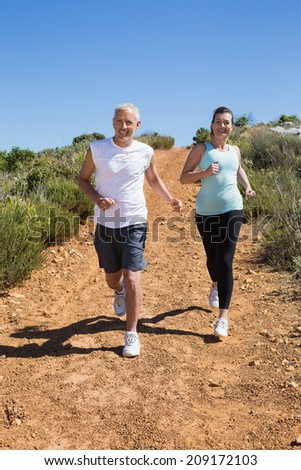 Fit smiling couple jogging down mountain trail on a sunny day - stock photo