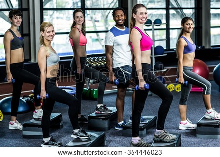 Fit smiling group doing exercise in gym - stock photo