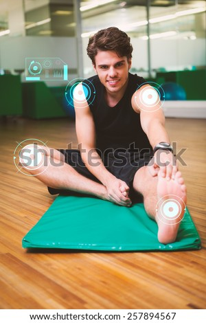 Fit smiling man warming up in fitness studio against fitness interface - stock photo
