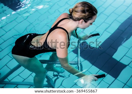 Fit smiling woman cycling on a swimming bike in swimming pool - stock photo