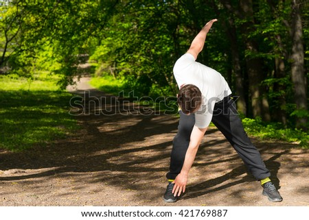 Fit Sportsman Limbering Up Stretching His Muscles Before Commencing His Workout In The Park - stock photo