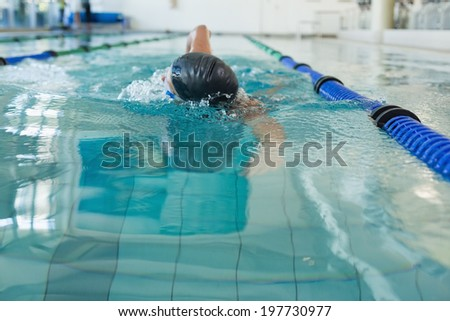 Fit swimmer doing the front stroke in the swimming pool at the leisure center - stock photo