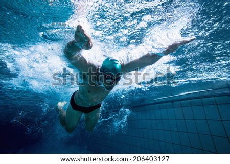 Fit swimmer training by himself in the swimming pool at the leisure centre - stock photo