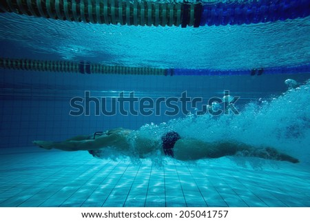 Fit swimmer training on his own in the swimming pool at the leisure centre - stock photo