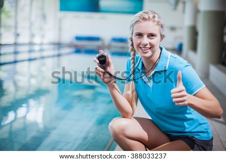 Fit trainer showing stopwatch with thumbs up at the pool - stock photo
