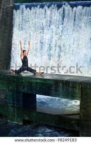 Fit white man doing the splits on concrete footbridge at the waterfall - stock photo