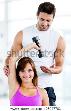 Fit woman at the gym with a personal trainer - stock photo