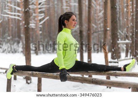 Fit woman athlete doing left leg split stretching exercises outdoors in woods. Female sports model exercising outdoor winter park. - stock photo