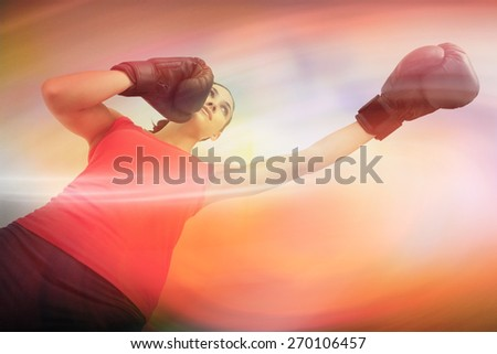 Fit woman boxing against purple and orange sky - stock photo