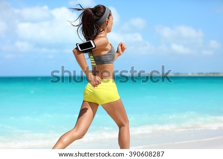 Fit woman cardio training doing running workout on beach. Unrecognizable athlete runner jogging fast on summer ocean background wearing a phone armband holder for music listening on smartphone app. - stock photo