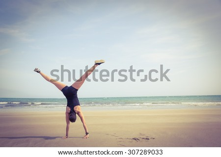 Fit woman cartwheeling on the sand at the beach - stock photo