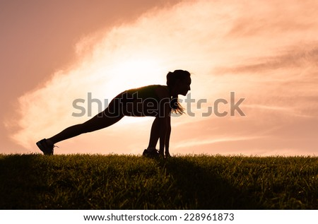Fit woman doing stretching exercises outdoors - stock photo