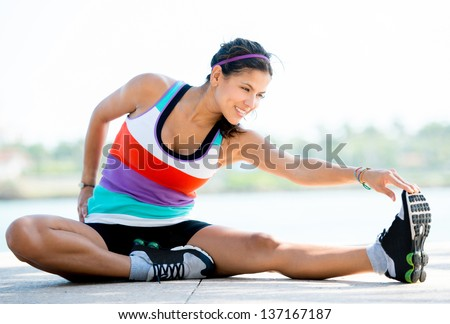 Fit woman doing stretching exercises outdoors and smiling - stock photo