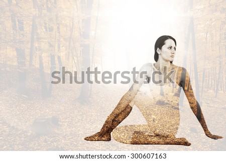 Fit woman doing the half spinal twist pose in fitness studio against autumnal forest - stock photo