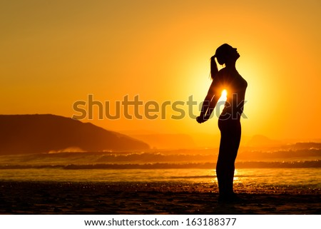 Fit woman doing yoga relaxing and breathing exercises on beach at sunset. Freedom, relax and harmony in nature. Female stretching arms alone. - stock photo