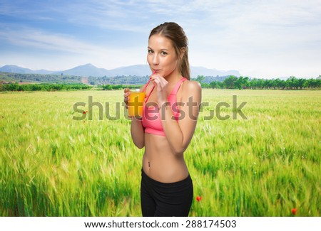 Fit woman drinking a orange juice - stock photo