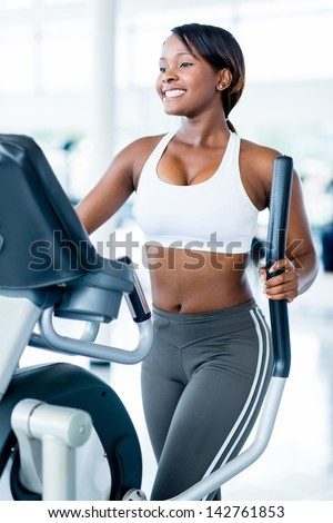 Fit woman exercising at the gym on an xtrainer - stock photo