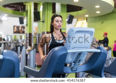Fit woman exercising on treadmill in gym - stock photo
